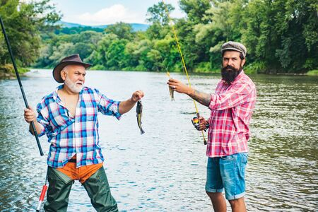 Man fisherman catches a fish. Fly fishing for trout. Fly fishing is most renowned as a method for catching trout grayling and salmon.