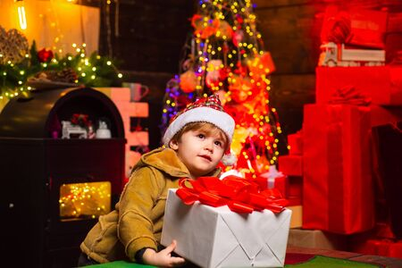 Cute little kid boy play near christmas tree. Kid enjoy winter holiday at home. Home filled with joy and love. Best wishes for you your family this christmas. Merry christmas and happy new year