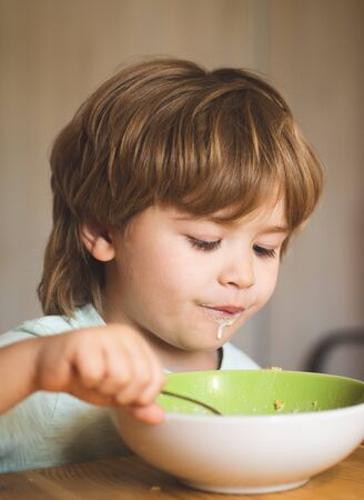 Kid eating. Little boy having breakfast in the kitchen.