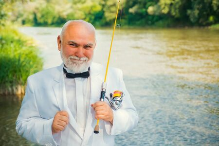 Fly fishing for trout. Brown trout being caught in fishing net. Portrait of cheerful man fishing. Fly angler man on the river. Fishing in river. Stock Photo