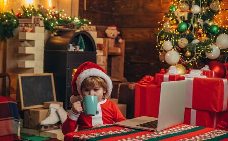 Boy child with laptop near christmas tree. Buy christmas gifts online. Christmas shopping concept. Gifts service. Little genius. Santa little helper. Little boy santa hat and costume having fun