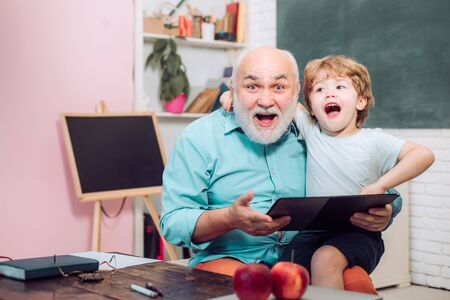Teacher and pupil learning together in school. Teachers day. Portrait of grandfather and grandson on blackboard in classroom. Portrait of confident old male teacher.