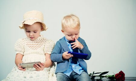 social net in phone. small kid with red rose. formal little boy and girl. friendship relations. children couple in love. romantic couple on date. valentines day. happy childhood. family bond. vintage 写真素材