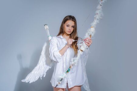 Valentines day cupid. The God of Love. Postcard for Valentines Day - copy space. Cute little female cupid shoots a bow. Innocent girl. Sweet girl wearing angel costume white dress and feather wings. Stock fotó