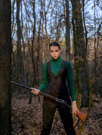female hunter in forest. successful hunt. hunting sport. military fashion. achievements of goals. girl with rifle. chase hunting. Gun shop. woman with weapon. Target shot. hunter aiming rifle nature Stockfoto