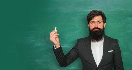 Good teachers enjoy teaching. Bearded professor at school lesson at desks in classroom. Chalkboard copy space. Female Teacher poin on blackboard.