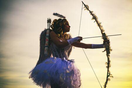 Eine Silhouette eines Bogenschützen, der einen Pfeil in Richtung eines bunten Himmels abfeuert. Süßes Mädchen des Amors mit einem Bogen. Engelskindermädchen mit dem gelockten blonden Haar. Festliche Kunst-Grußkarte. Pfeil der Liebe.