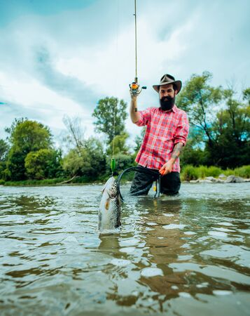 Fly fishing for trout. Fishing in river. Catches a fish. Catching a big fish with a fishing pole. Fly fishing - method for catching trout. Stockfoto