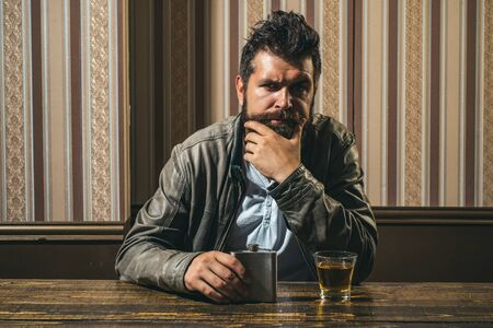 Man with beard holds glass brandy. Man holding a glass of whisky. Handsome stylish bearded man is drinking whiskey. Barbershop, shaving. Thinking to drink or not to drink.