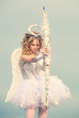 Ein Kind in der Kleidung eines Engels auf Himmelshintergrund. Der Gott der Liebe. Valentinstag. Engelsflügel baby. Unschuldiges Mädchen mit Engelsflügeln, das mit Pfeil und Bogen gegen blauen Himmel und weiße Wolken steht Standard-Bild