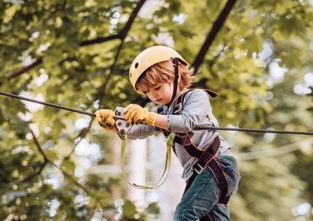Portrait of a beautiful kid on a rope park among trees. Beautiful little child climbing and having fun in adventure Park. Children fun. Playground. Child playing on the playground. Stock Photo