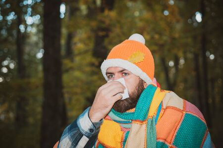 Man work out after he Sick blowing nose and sneezing, coughing. Infected man blowing his nose in tissue paper because of being ill or allergy. Portrait of man in autumn clothes with allergy or cold. Imagens