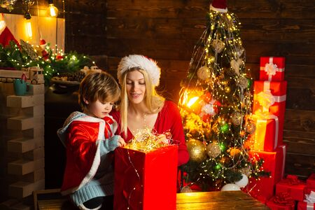 Family having fun at home christmas tree. Mom and kid play together christmas eve. Family holiday. Happy family. My dear baby santa. Mother and little child boy adorable friendly family having fun