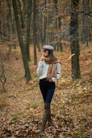 Relaxing smoking. Woman enjoy smoking alone. Autumnal melancholy. Autumn is here. Pretty woman in hat and sunglasses smoking cigarette forest background. Fall fashion accessory. Enjoy fall season Stock fotó