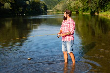 Man fishing. Fly fisherman using fly fishing rod in beautiful river. Man with fishing rods on river berth. Concepts of successful fishing. Stock Photo
