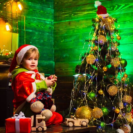 Merry christmas and happy new year. Cute boy play near christmas tree. Kid enjoy winter holiday at home. Home filled with joy and love. Make wish. Best wishes for you your family this christmas 스톡 콘텐츠 - 126957837