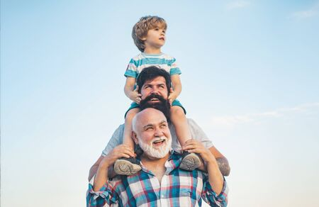 Men generation: grandfather father and grandson are hugging looking at camera and smiling. Fathers day concept. Generation concept. Weekend family play. Men in different ages. 版權商用圖片