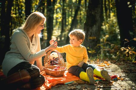 Insegnare al figlio una sana alimentazione. Facendo un'escursione picnic con merenda. Infanzia felice. Mamma e bambino che si rilassano mentre fanno un'escursione nella foresta. Picnic in famiglia. Madre bella donna e figlio piccolo che si rilassano un picnic nella foresta Archivio Fotografico