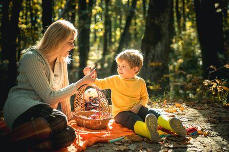 Zoon gezonde voeding leren. Met snack picknick wandeling. Gelukkige jeugd. Moeder en kind jongen ontspannen tijdens het wandelen in het bos. Familie picknick. Moeder mooie vrouw en zoontje ontspannende bospicknick Stockfoto