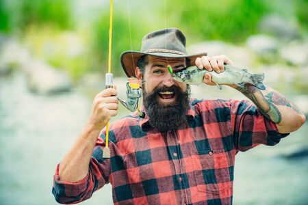 Catches a fish. Fishes catching hooks. Fishing in river. Fly fishing for trout. Rainbow trout on a hook. Fly rod and reel with a brown trout from a stream. Stock Photo