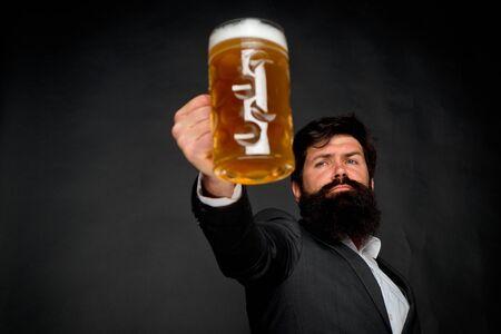 Offenes Lächeln des sexy bärtigen Mannes und großen Becher Bier in seiner Hand. Bier Zeit.
