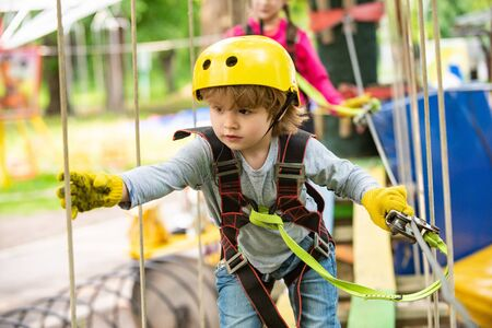 Children summer activities. High ropes walk. Every childhood matters. Happy little boy calling while climbing high tree and ropes. Safe Climbing extreme sport with helmet.