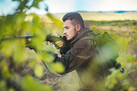 Hunter with shotgun gun on hunt. Hunter with Powerful Rifle with Scope Spotting Animals. Stock Photo