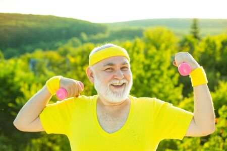 Happy Senior sportman exercising with lifting dumbbell on green park background. Reklamní fotografie