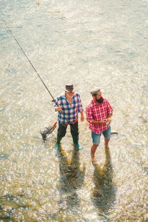 Portrait of cheerful two bearded men fishing. Man fisherman catches a fish. Fly fishing for trout. Angler. Father with son on the river enjoying fishing holding fishing rods.