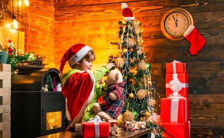 Cute boy play near christmas tree. Kid enjoy winter holiday at home. Home filled with joy and love. Make wish. Best wishes for you your family this christmas. Merry christmas and happy new year