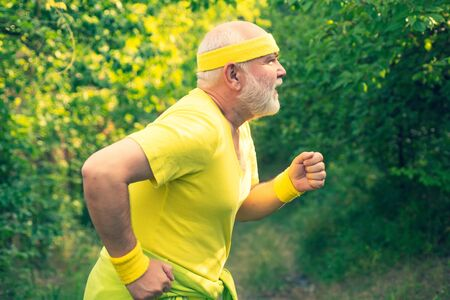 Senior runner in nature. Cardio workout. Running in park in the morning. Senior male is enjoying sporty lifestyle. Healthy lifestyle concept