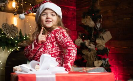 Portrait little girl with gift on wooden Christmas background. Cute little girl coming to Christmas tree and looks at her New Years gift. Children s wear trends in winter 2020. Stock Photo