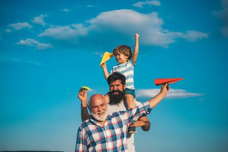 Portrait of happy father giving son piggyback ride on his shoulders and looking up. Dream of flying. Fathers day concept. Generation concept.