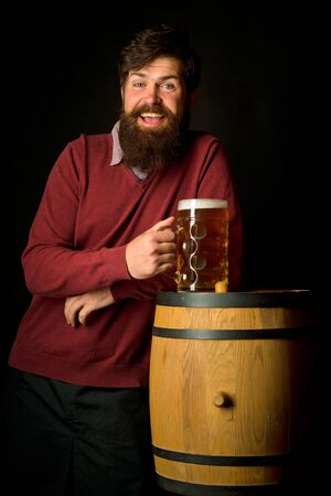 Man with beer. Germany - Bavaria. Beer. Happy smiling man with beer and Wooden barrel and glass of beer.