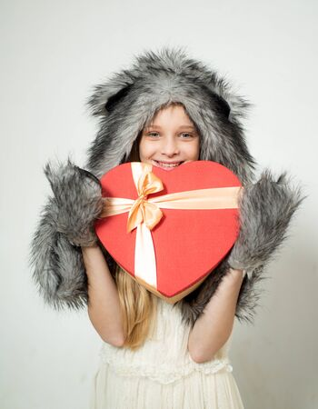 i love you. Small girl wear winter hat scarf. Winter fashion trends for kids. valentines day. present box in shape of heart. red heart. love. boxing day. valentines day shopping. present with love