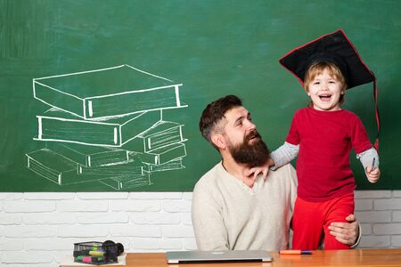 Man teacher play with preschooler child. Being joyful and thrilled. Back to school and Education concept. Blackboard copy space. Little students. Elementary school teacher and student in classroom Stok Fotoğraf