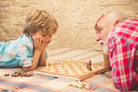 Chess piece. Grandfather and grandson concept. Handsome grandpa and grandson are playing chess while spending time together at home. Banco de Imagens