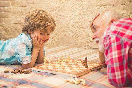 Pieza de ajedrez. Concepto de abuelo y nieto. Apuesto abuelo y nieto están jugando al ajedrez mientras pasan tiempo juntos en casa. Foto de archivo