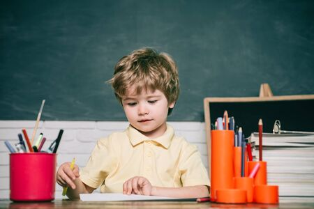 Child from elementary school with book and bag. Child is ready to answer with a blackboard on a background. Happy cute industrious child is sitting at a desk indoors.