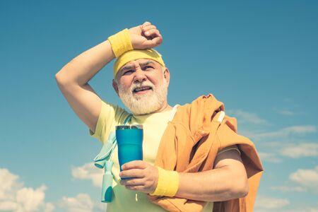 Energetic for elderly sportsmen. Grandfather sportsman on blue sky backgrounds. Portrait of healthy senior sport man. Senior sportsman in sport center.