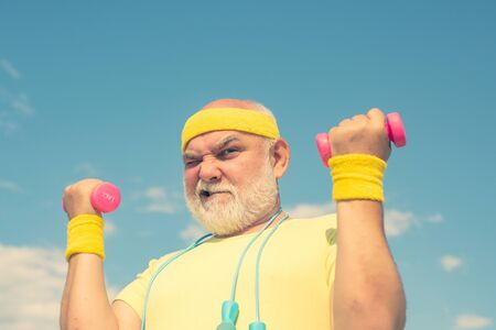 Funny Senior sportman exercising with lifting dumbbell on blue sky background. Isolated, copy space.