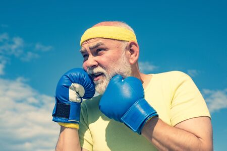 Senior men fighting poses. Grandfather doing boxing training in morning. Portrait of a determined senior boxer over blue sky background. Reklamní fotografie - 127791579