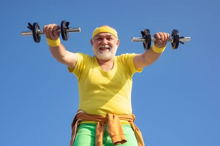 Senior man lifting weights. Senior man in gym working out with weights. Happy senior man with dumbbell looking at camera. Grandfather sportsman portrait on blue sky backgrounds.