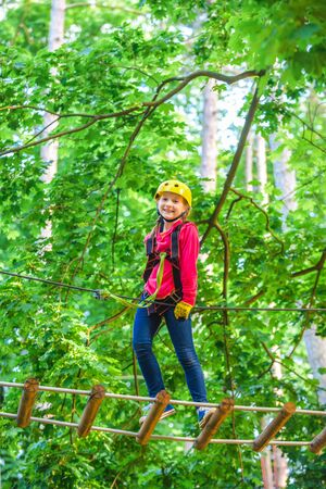 Beautiful little child climbing and having fun in adventure Park. Hiking in the rope park girl in safety equipment. Kid climbing trees in park. Cute child boy.