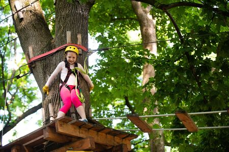 Kid climbing trees in park. Rope way - little girl is looking at the rope slideway fearing. Looking away with fear of extreme rope slide. Reklamní fotografie