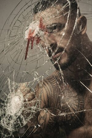 Brutal handsome macho focused on fight result. Want to fight right now. Fight concept. Man muscular body punching. Concentrated on target. Destroy obstacles. Handsome brutal man near broken glass