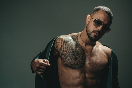 Fashionable tattoo. Muscular hispanic man with tattoo on chest. Strong latino man with tattoo on skin. Tattooed guy with muscle torso and tattoo Stock fotó