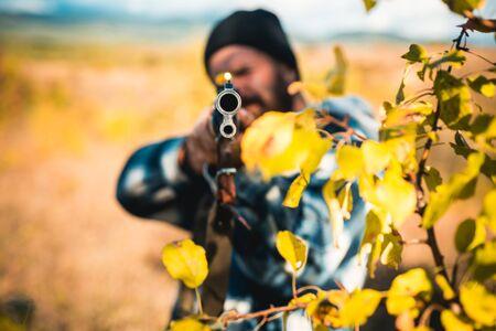 Hunter aiming rifle in forest. Autumn hunting season. Hunter with shotgun gun on hunt. Track down.