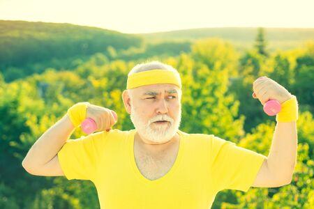 Großvater Sportlerportrait. Älterer Sportler, der mit anhebender Hantel auf grünem Parkhintergrund trainiert.