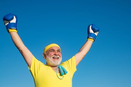 Happy Senior man wearing boxing gloves. Portrait of a determined senior boxer over blue sky background. Healthy fighter senior old man boxing gloves.